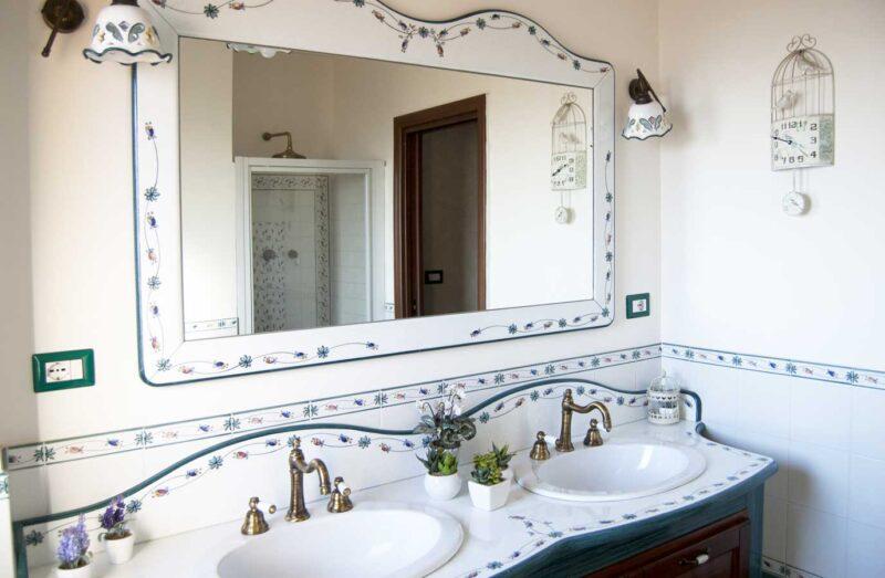 bagno con doppio lavabo in pietra lavica con decoro semplice