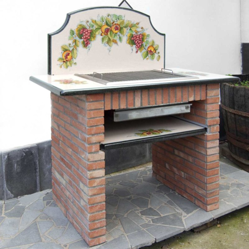 Barbecue in muratura con top e piano in pietra lavica decorato a mano