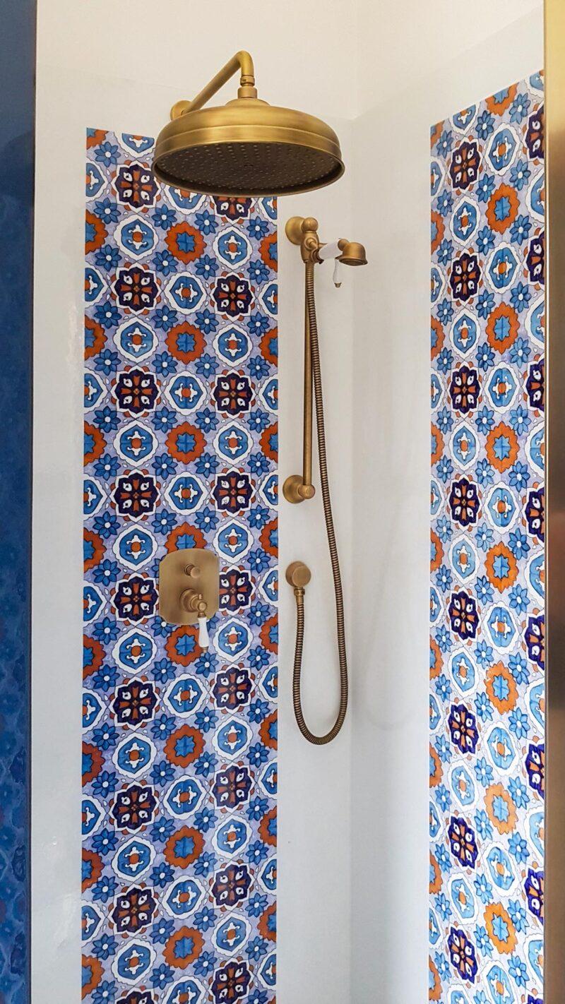 Zona doccia con rivestimento in pietra lavica decorata a mano