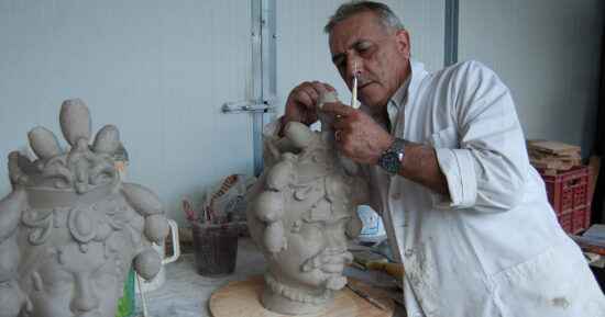 Il Maestro Giuseppe Sorbello  nel suo Atelier di Macchia di Giarre mentre modella l'argilla per la  creazione di una testa di Moro uomo
