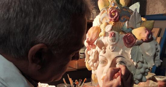 Il Maestro Giuseppe Sorbello nel suo Laboratorio di Ceramica Artistica di Macchia di Giarre,  mentre si dedica alla decorazione delle Teste di Moro Siciliane con particolare cura alla colorazione degli occhi.