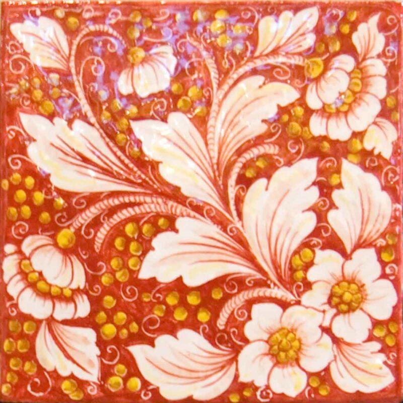 mattonella decorata a mano con fondo rosso e fiori bianchi