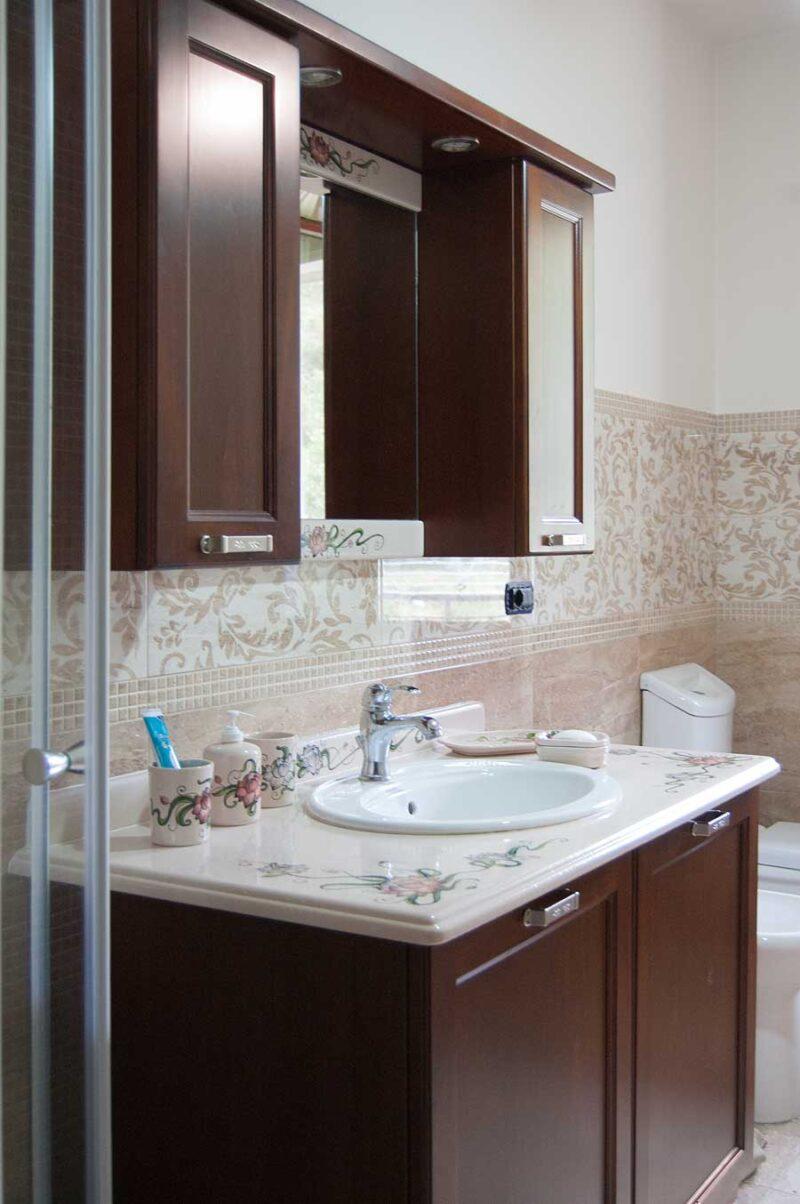 mobile bagno con ante e pensili in legno massello, top in pietra lavica decorato a mano