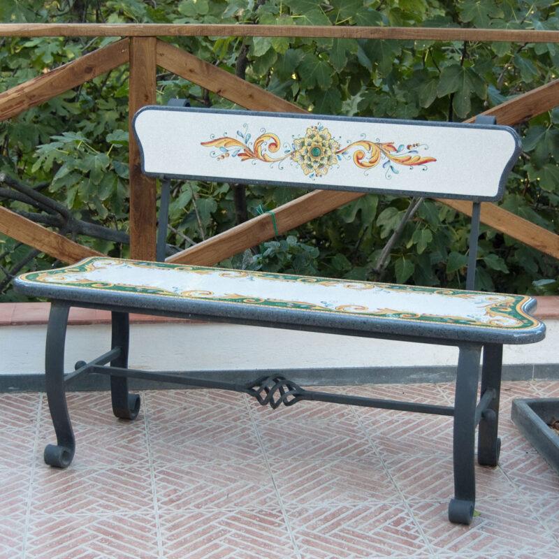 panchina in ferro con seduta e schienale in pietra lavica decorata a mano