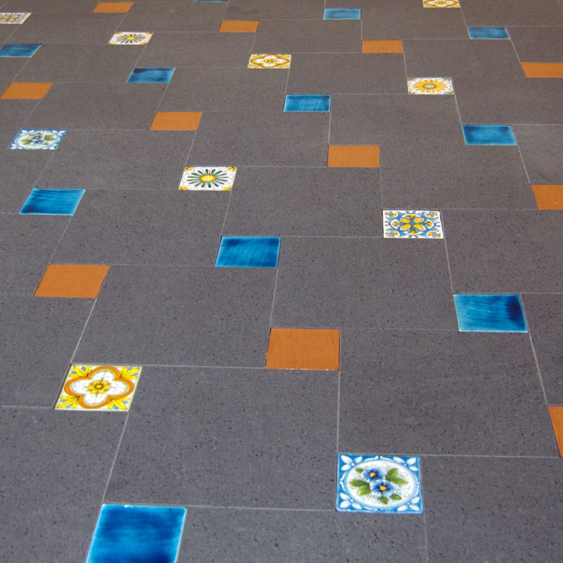 pavimento in pietra lavica con mattonelle decorate a mano