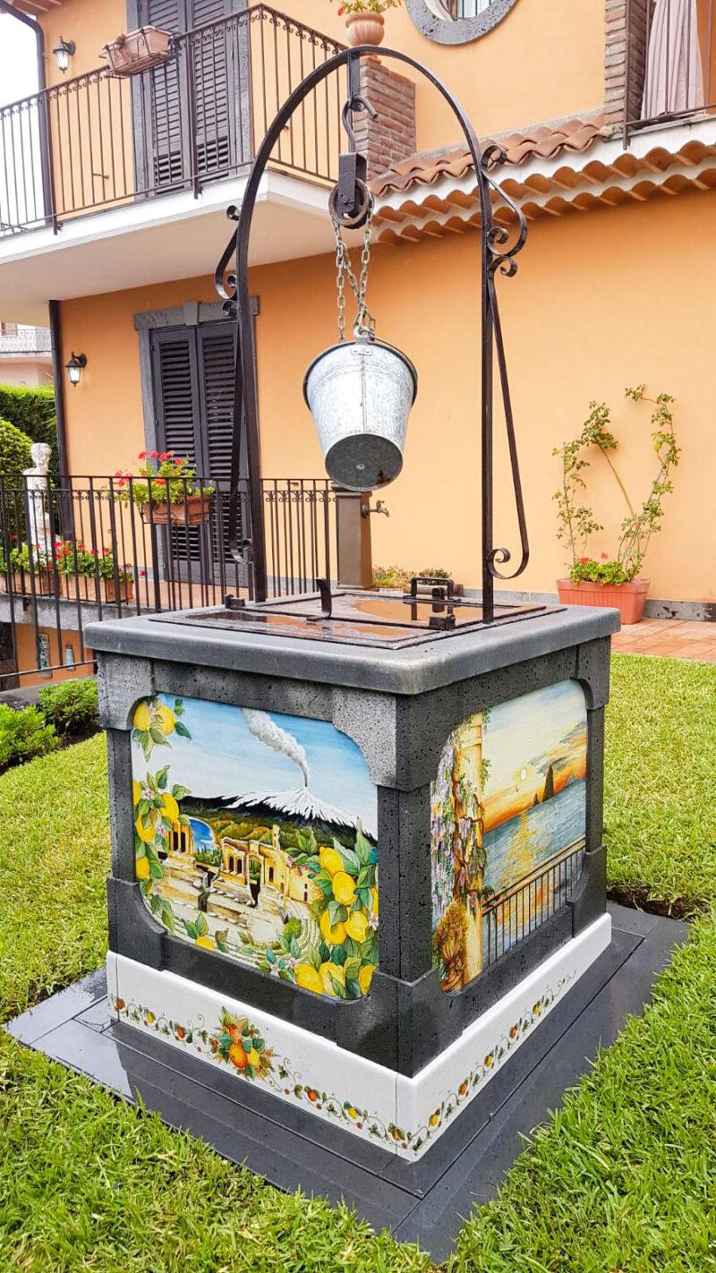 Pozzo con rivestimento e pannelli in pietra lavica decorati a mano