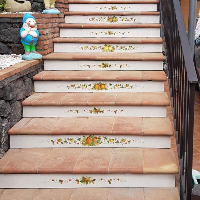 Scala con pedata in cotto e alzata in pietra lavica decorata a mano