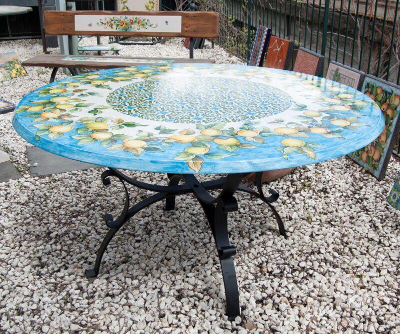 tavolo da giardino in pietra lavica con decoro limoni e base in ferro battuta